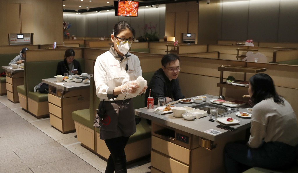 In this March 5, 2020, photo, a waitress of the Chinese restaurant Hot Pot wearing a face mask, serves customers in London. While white collar workers...