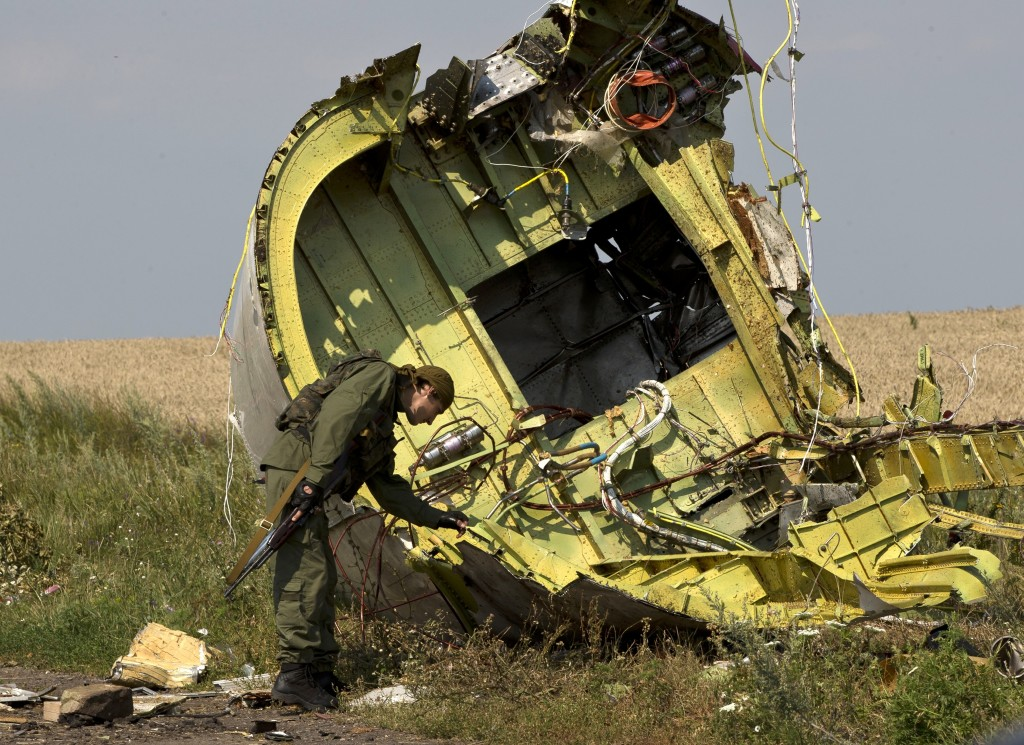 FILE - In this July 22, 2014 file photo, a pro-Russian rebel touches the MH17 wreckage at the crash site of Malaysia Airlines Flight 17, near the vill...