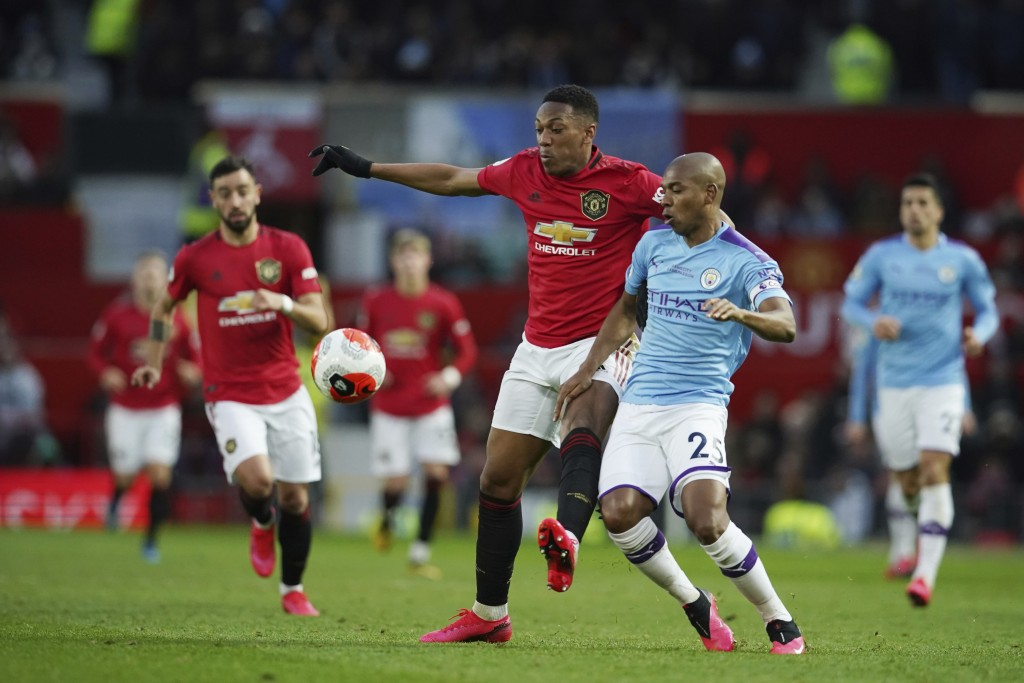 Manchester United's Anthony Martial, center, and Manchester City's Fernandinho compete for the ball during the English Premier League soccer match bet...