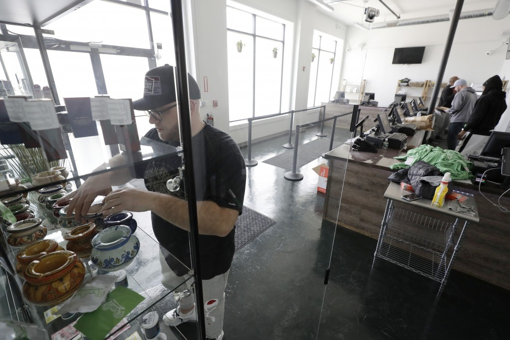 Mike Whittaker, of Quincy, Mass., left, director of operations at Pure Oasis recreational marijuana shop, arranges products on a shelf in the store, S...