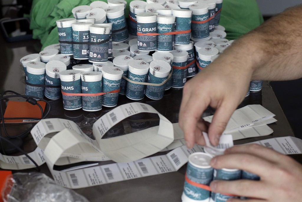 Mike Whittaker, of Quincy, Mass., director of operations at Pure Oasis recreational marijuana shop, applies bar codes to containers of cannabis flower...