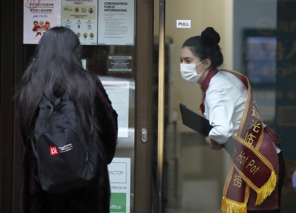 In this March 5, 2020, photo, a waiter of a Chinese restaurant wearing a face mask welcomes a customer in London. While white collar workers trying to...
