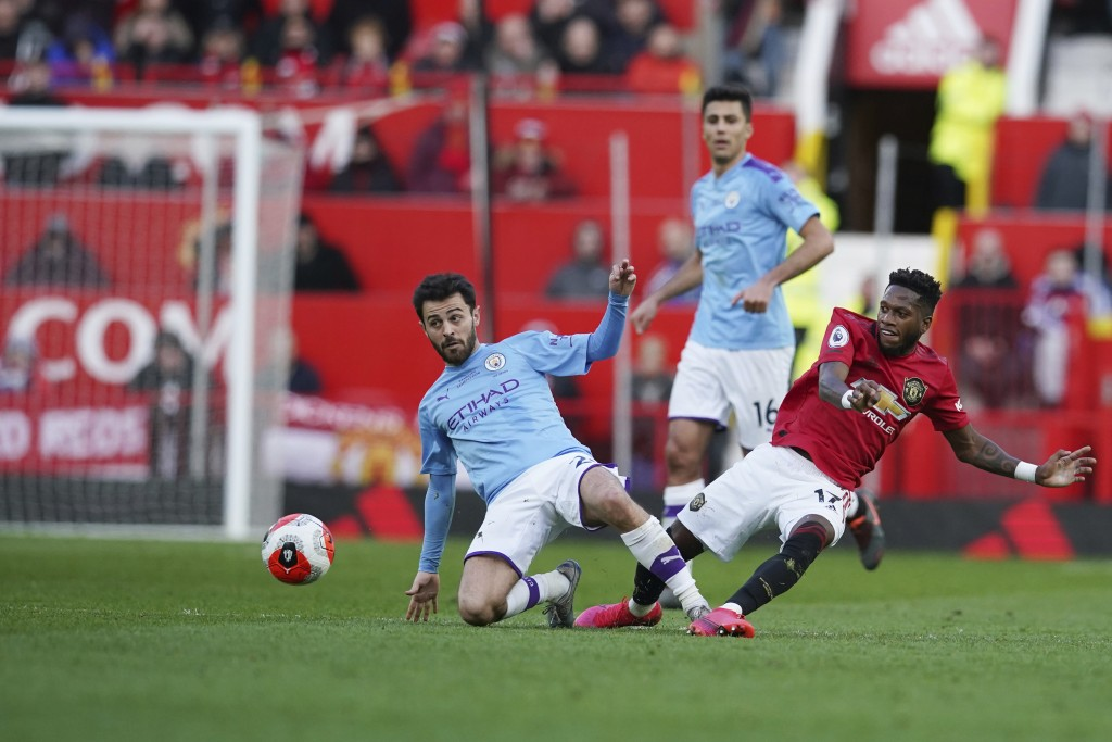 Manchester City's Bernardo Silva, left, and Manchester United's Fred compete for the ball during the English Premier League soccer match between Manch...