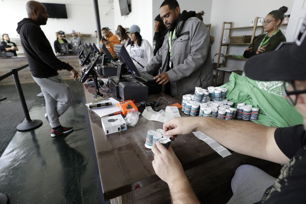 Mike Whittaker, of Quincy, Mass., below right, director of operations at Pure Oasis recreational marijuana shop, applies bar codes to containers of ca...