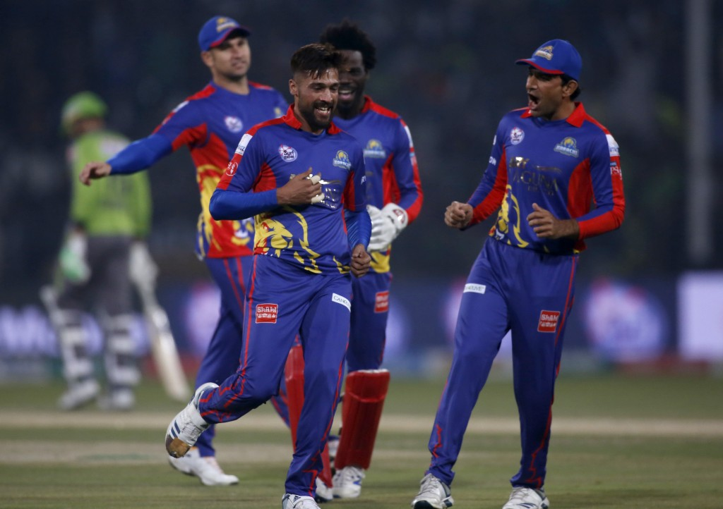 Karachi Kings pacer Mohammad Amir, center celebrates with teammates after taking the wicket of Lahore Qalandars batsman Fakhar Zaman during a Pakistan...