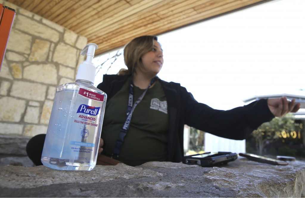In this photo made Friday, March 6, 2020, a bottle of hand sanitizer sits next to ticket taker Mariah Bernal as she hands back tickets to a patron ent...
