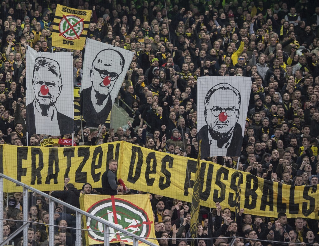 Visitors show banners with the faces of Dietmar Hopp, Fritz Keller and Karl-Heinz Rummenigge with red clown's noses during the German Bundesliga socce...