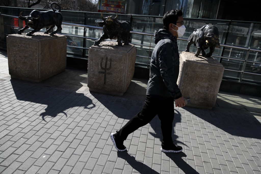 A man wearing a protective face mask walks by statues of bulls on display outside a bank in Beijing, Tuesday, March 10, 2020. Asian stock markets took...