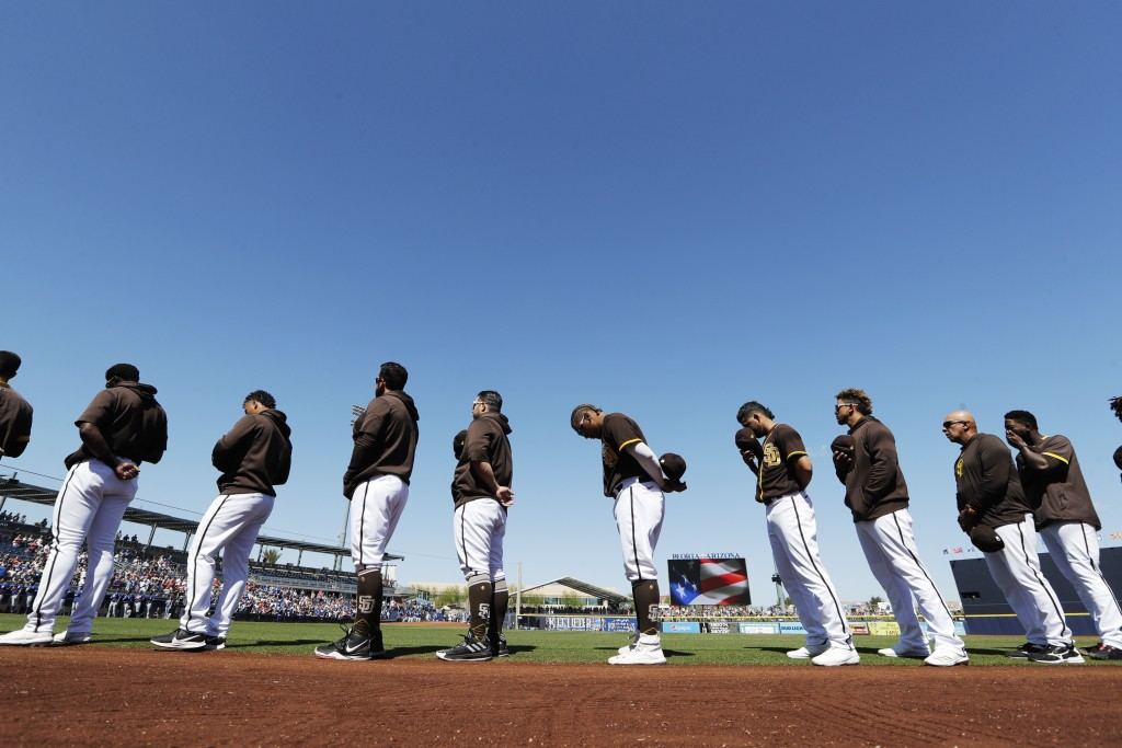 San Diego Padres players and coaches line up during playing of the national anthem before a spring training baseball game against the Los Angeles Dodg...