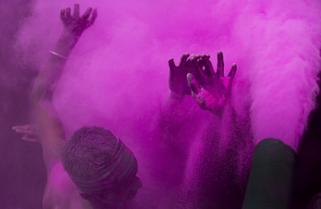 Indians dance and throw colored powder during Holi festival celebrations in Gauhati, India, Tuesday, March 10, 2020. The festival heralds the arrival ...