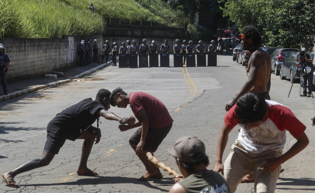 Guarani Mbya indigenous men dance as they wait for police to enter the property they have been occupying for just over a month in an attempt to stop r...