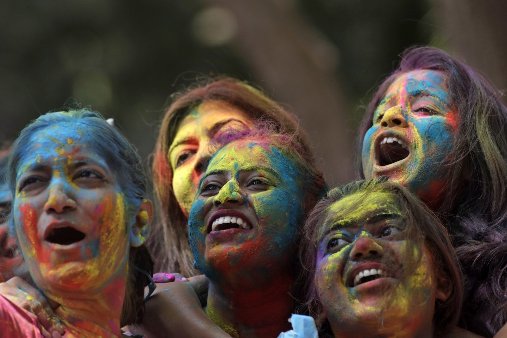 Women with their faces smeared with colored powder cheer during celebrations marking the Holi festival in Mumbai, India, Tuesday, March 10, 2020. Holi...
