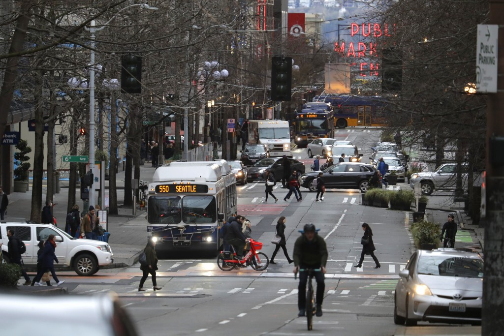 In this March 6, 2020 photo, bus, bike, pedestrian and car traffic is light on Pike St. in downtown Seattle at 5:20 pm during the Friday evening commu...