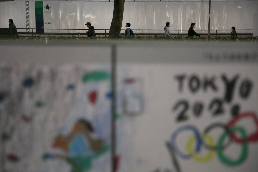 FILE - In this March 3, 2020, file photo, commuters walk along a sidewalk as a poster celebrating the Tokyo 2020 Olympics is seen in foreground in Tok...