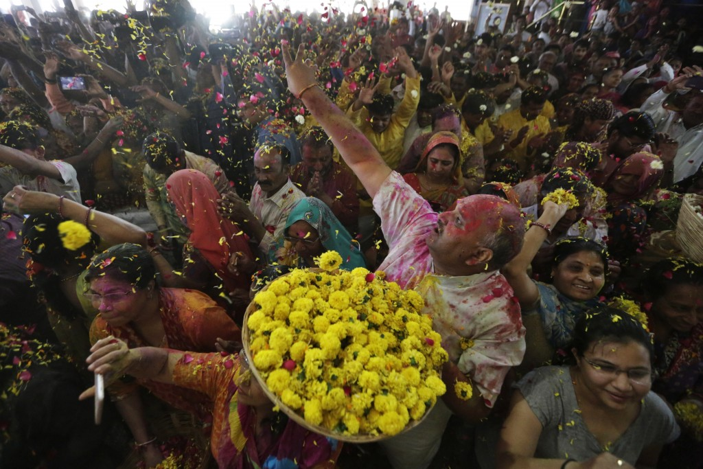 A Indian man throws flowers out to devotees during Holi festival celebration at the Lord Jagannath temple in Ahmedabad, India, Tuesday, March 10, 2020...