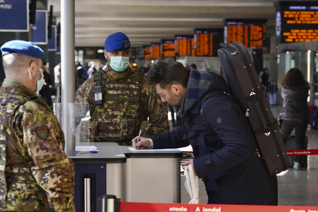A traveler fills out a form at a check point set up by border police inside Rome's Termini train station, Tuesday, March 10, 2020. In Italy the govern...