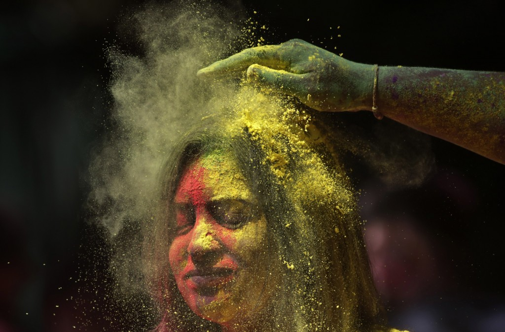 A man smears the face of a woman with colored powder during celebrations marking the Holi festival in Mumbai, India, Tuesday, March 10, 2020. Holi, th...