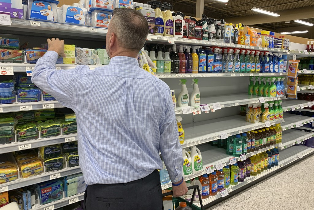 A customer looks for scrubbing pads near empty shelves of cleaning supplies at a Publix Supermarket amid concern over the COVID-19 virus on Monday, Ma...