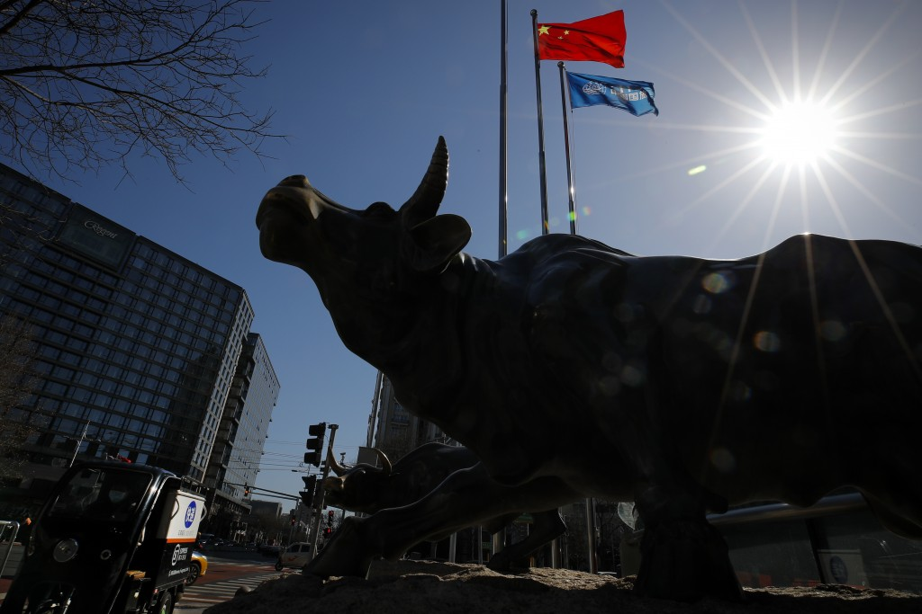 A delivery worker ride his cart passes by the investment icon bull statue on display outside a bank in Beijing, Tuesday, March 10, 2020. Asian stock m...