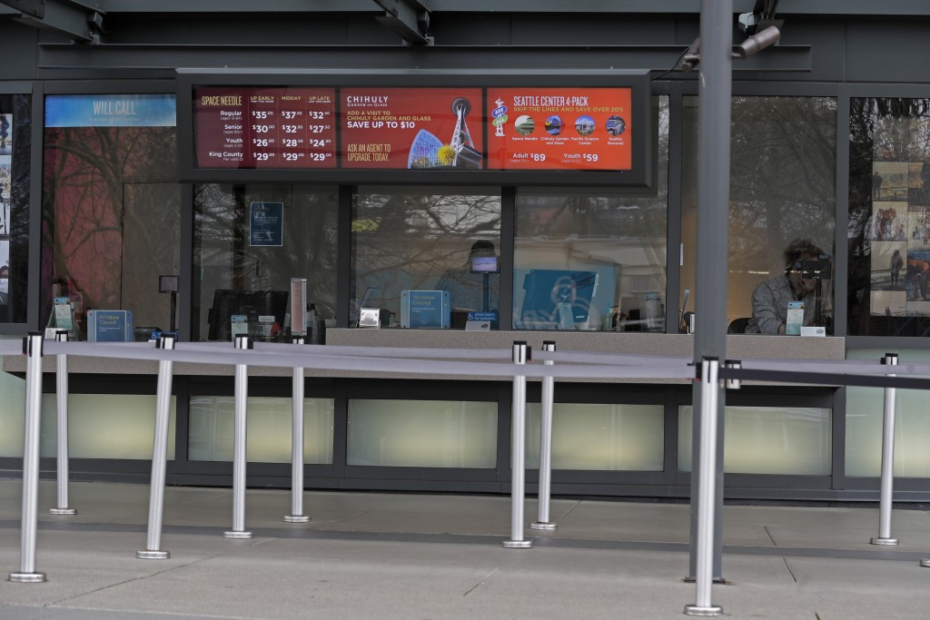 In this March 6, 2020 photo, a person waits for customers as they work in the ticket office for the Space Needle and other attractions at the Seattle ...