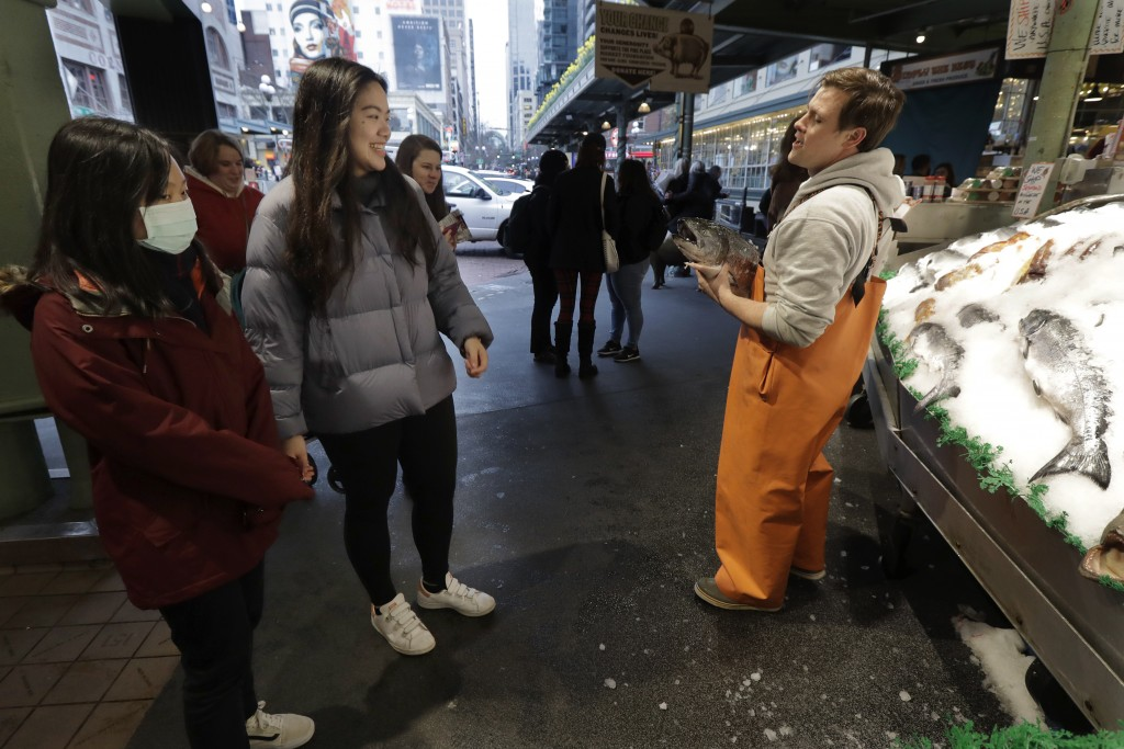 In this March 6, 2020 photo, a woman wears a mask as she joins a few others in watching Colin Kiplinger, right, as he works at Pike Place Fish Market ...