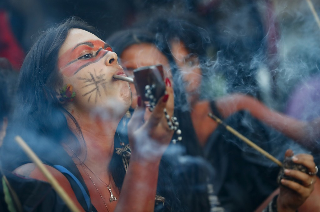 A member of the Guarani Mbya indigenous tribe smokes a pipe while waiting for police to enter the property the group has been occupying for just over ...