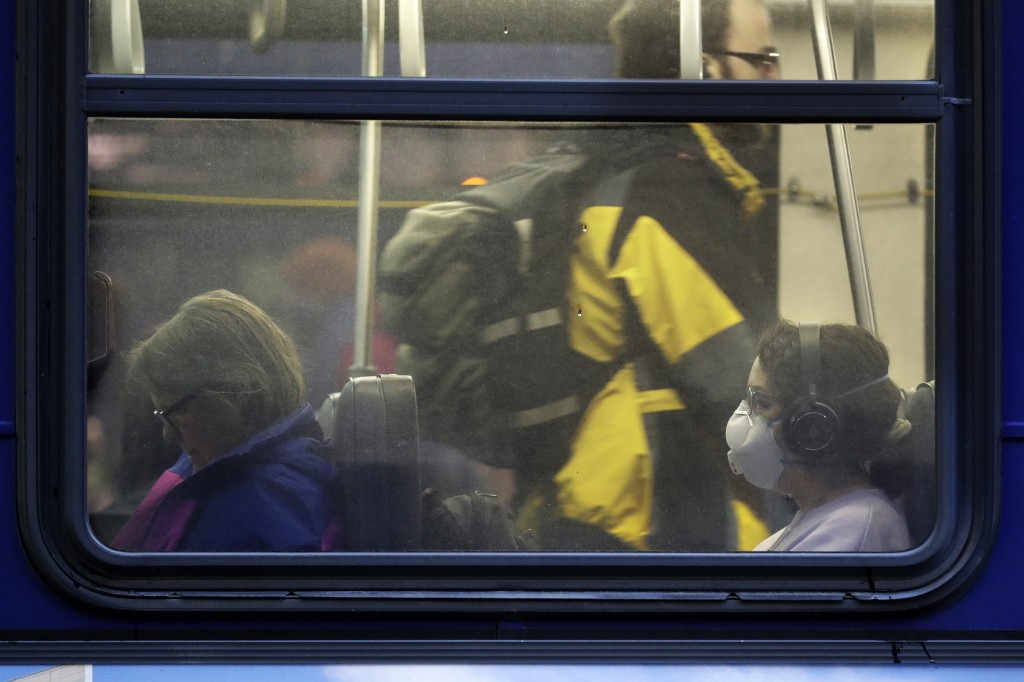 In this March 6, 2020 photo, a woman wears a mask as she rides a bus in downtown Seattle during the Friday evening commute. Many of the region's big e...
