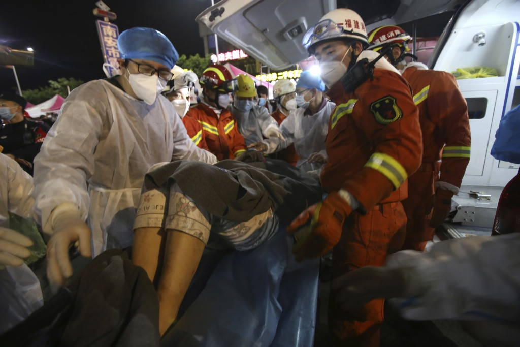 In this March 9, 2020, photo released by Xinhua News Agency, rescuers carry a woman pulled from the rubbles of a collapsed hotel to an ambulance in Qu...