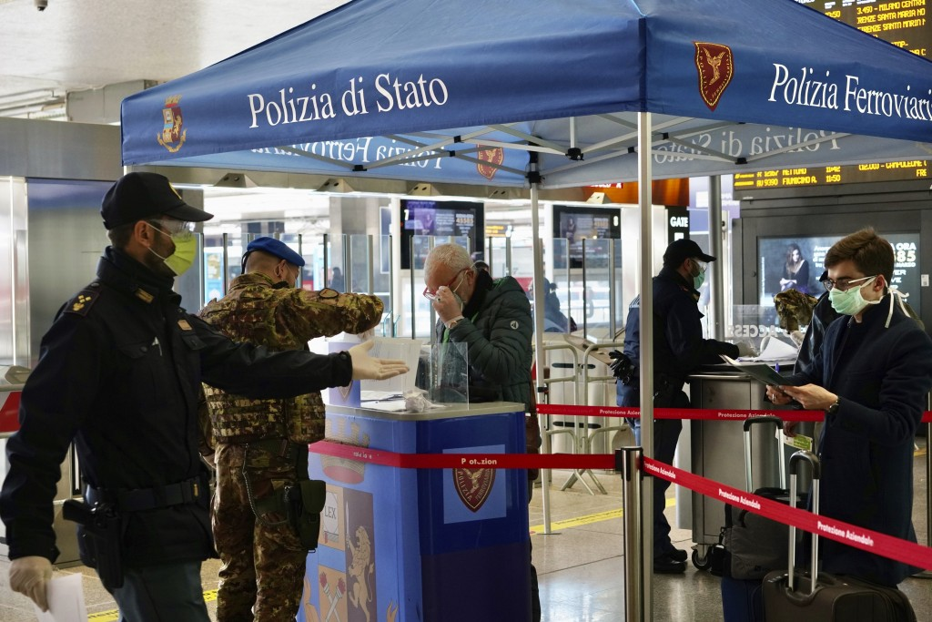 Border police check travelers documents at a check point inside Rome's Termini train station, Tuesday, March 10, 2020. In Italy the government extende...