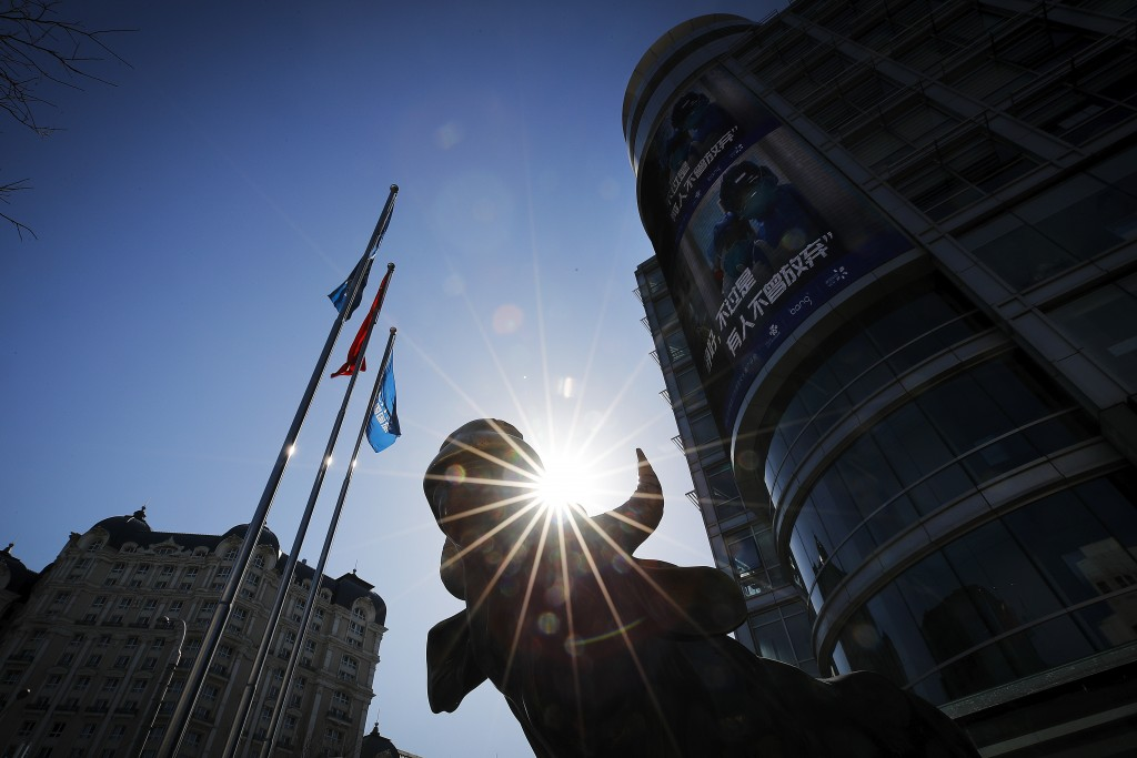 A statue of a bull, an investment icon, stands outside an office building with a screen showing propaganda about fighting against Coronavirus in Beiji...
