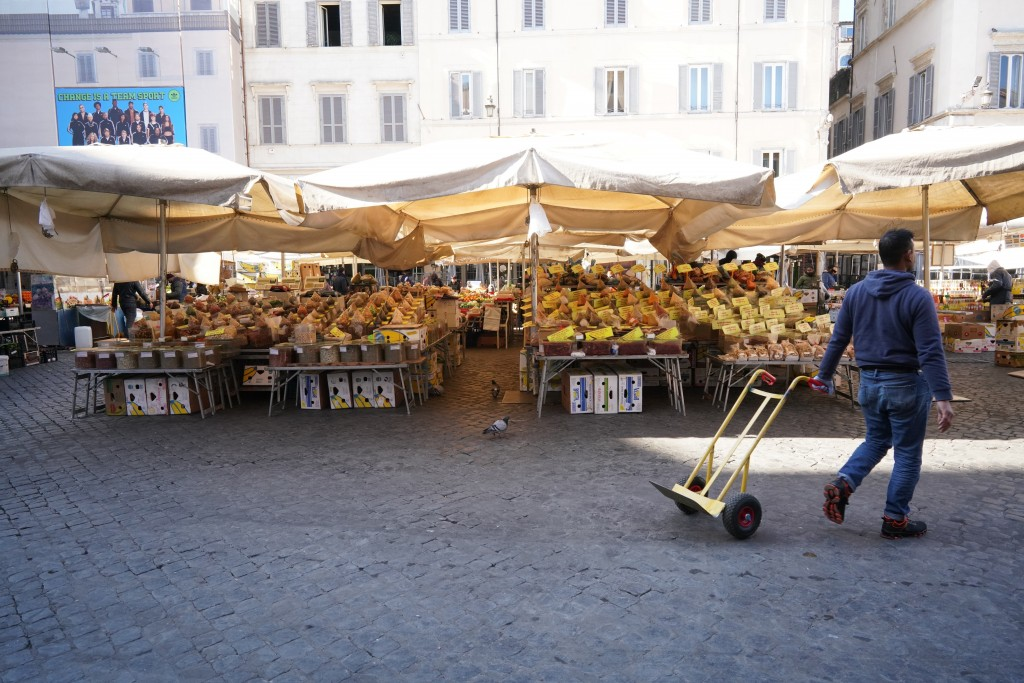 A man pulls a trolley at an emtpy Campo dei Fiori open-air market, in Rome, Tuesday, March 10, 2020. The Italian government is assuring its citizens t...