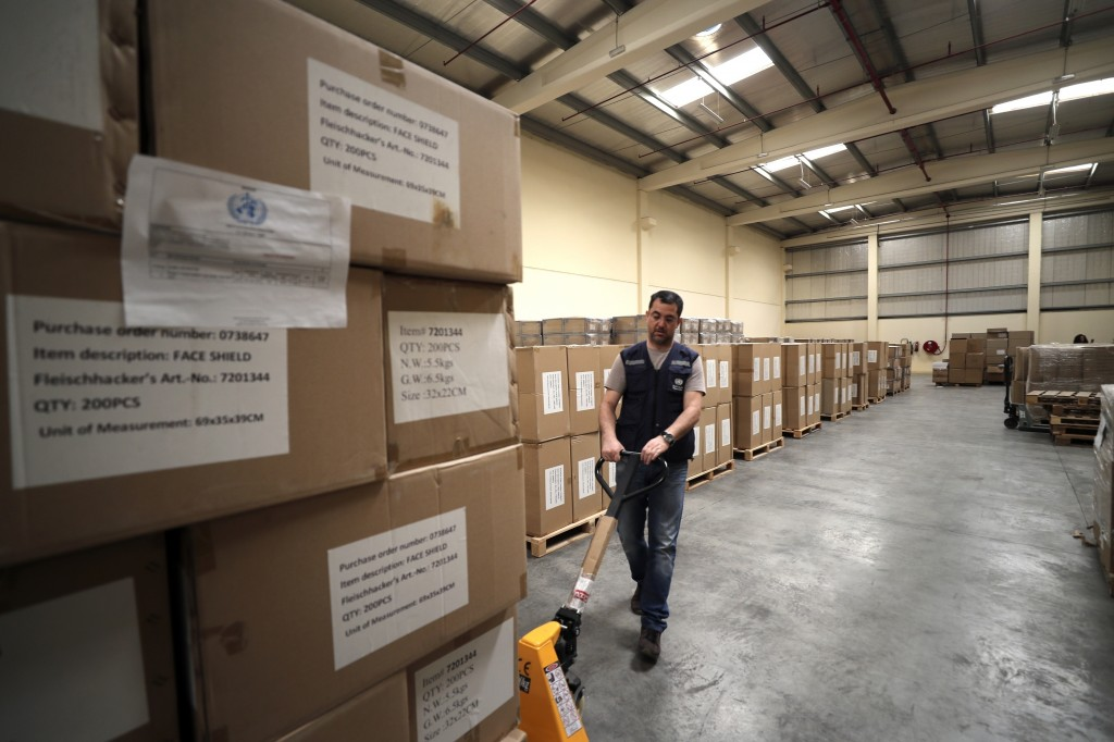 FILE -  In this March 5, 2020, file, photo, a worker pulls a cart of coronavirus aid items being prepared for shipment, at a World Health Organization...