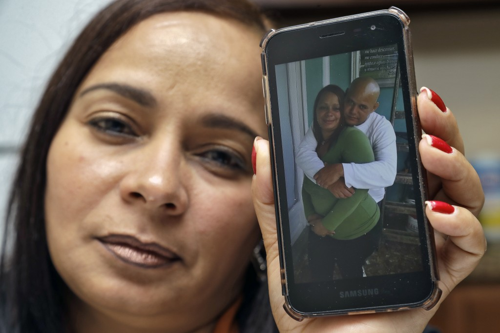In this Wednesday, Feb. 26, 2020 photo, Yarelis Gutierrez Barrios holds up a cell phone photo at her home in Tampa, Fla., of herself with her partner ...
