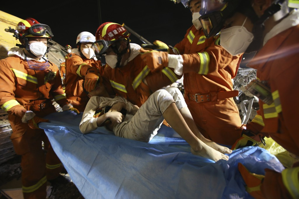 In this March 9, 2020 photo released by Xinhua News Agency, rescuers place a boy pulled from the rubbles of a collapsed hotel on a stretcher in Quanzh...