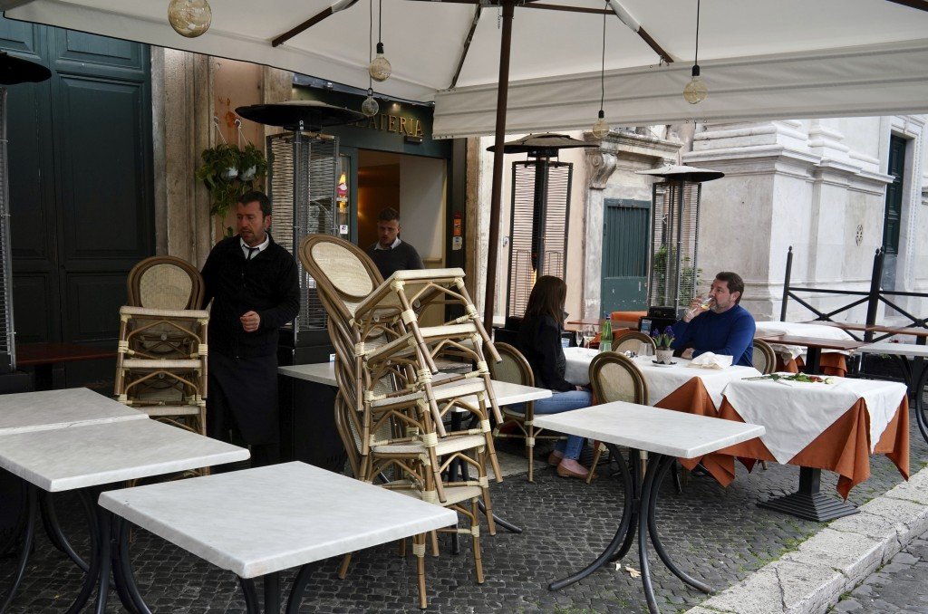 Waiters pile up chairs and prepare to close, according to the Italian government measures to slow down the diffusion of the new Coronavirus, at an hou...