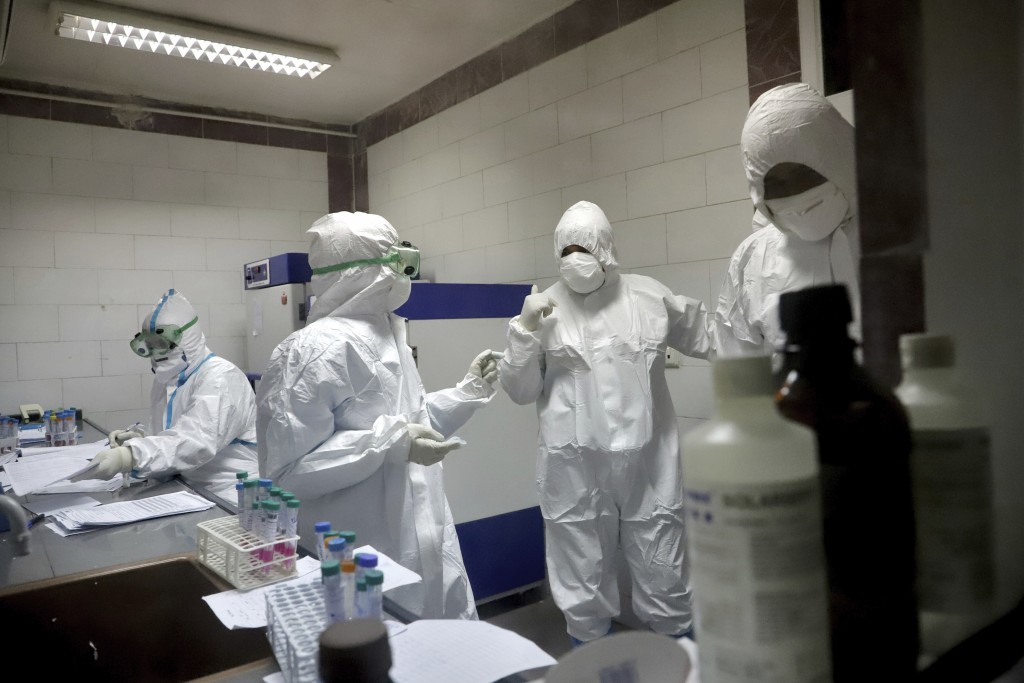 In this Tuesday, March, 10, 2020 photo, paramedics work in a laboratory that tests samples taken from patients suspected of being infected with the ne...