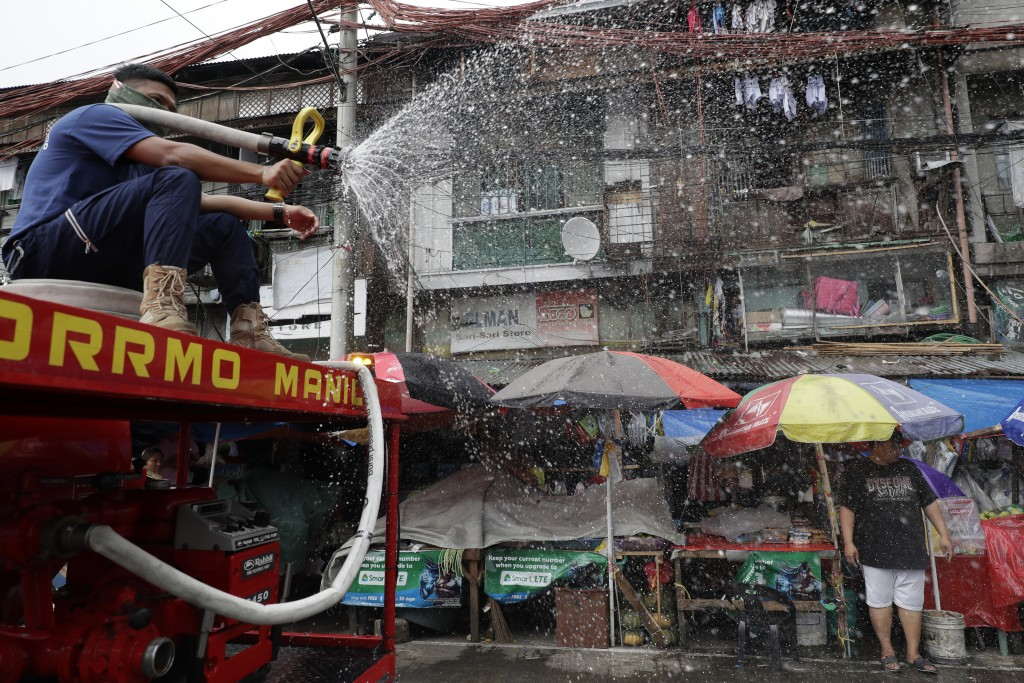 A fireman sprays disinfectant along a road in Manila, Philippines on Wednesday, March 11, 2020. For most people, the new coronavirus causes only mild ...