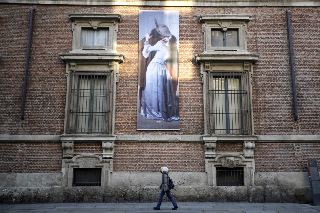 A woman walks past a poster depicting the 1859 painting by Italian artist Francesco Hayez, ll Bacio (The Kiss), hanging on a facade of the Pinacoteca ...