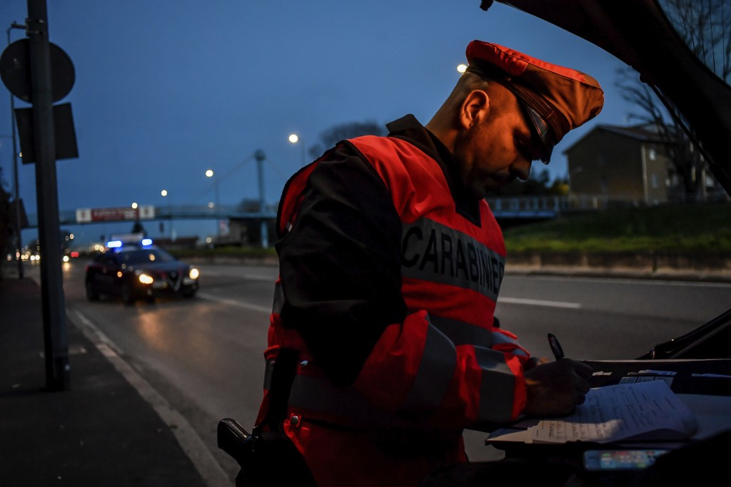 A policeman checks cars entering Milan, Northern Italy, Tuesday, March 10, 2020. People moving from one place to another must certificate they are doi...
