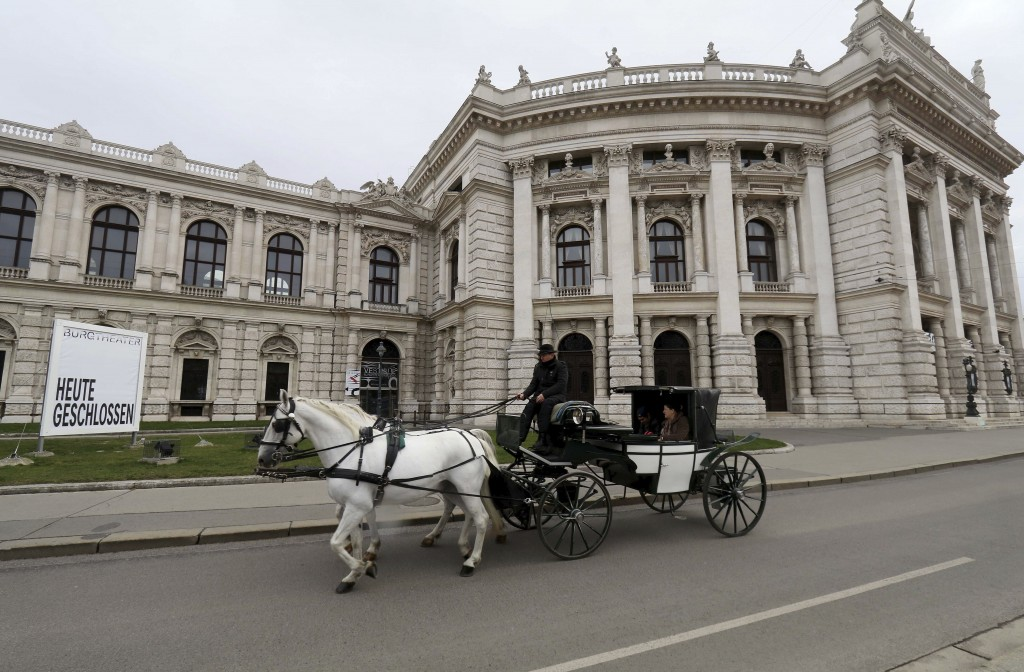 "A Fiaker coach passes in front of a poster is written "" closed today"" the Burgtheater in Vienna, Austria, Wednesday, March 11, 2020. The culture activ..."
