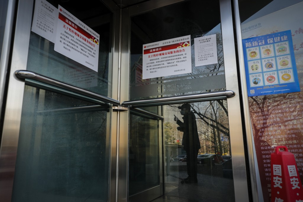 A man is reflected on a glass door of a stock brokerage that was closed except for limited transactions conducted through the glass of its front doors...