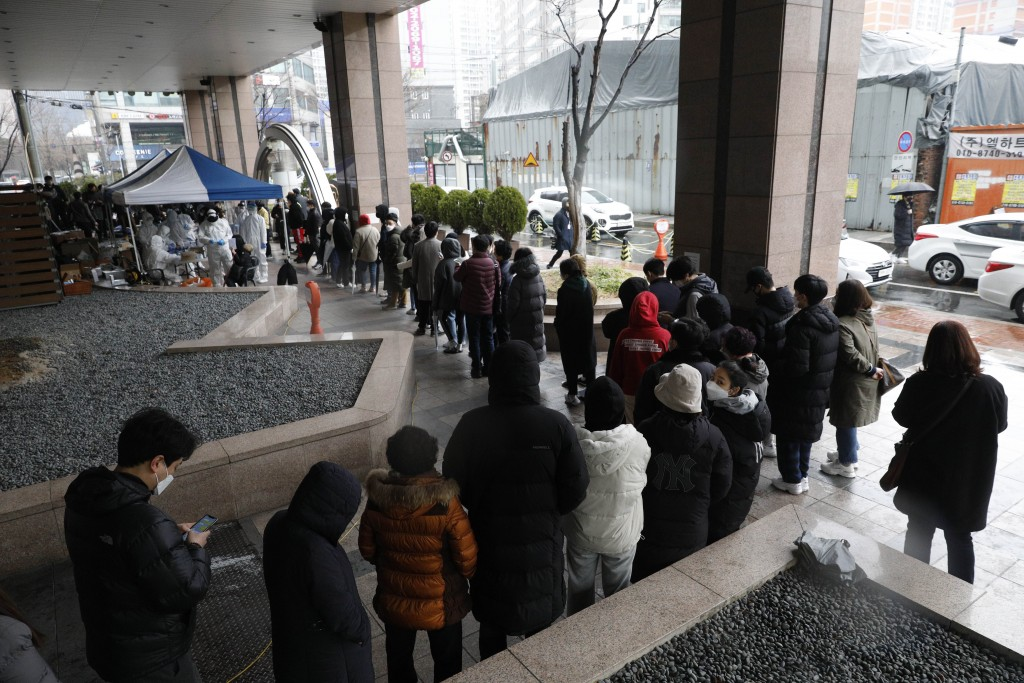 In this March 10, 2020, photo, people queue in a line for the virus test outside of the Korea Building where its call center is located in Seoul, Sout...