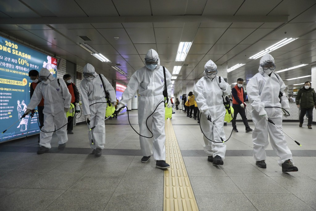 Workers wearing protective gears disinfect as a precaution against the new coronavirus at the subway station in Seoul, South Korea, Wednesday, March 1...