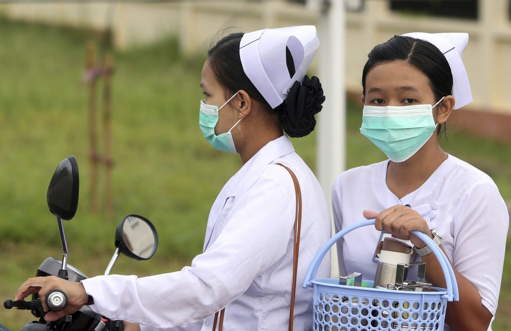 FILE - In this July 25, 2017 file photo, nurses cover their faces with masks to protect from the spread of the swine flu outside the Naypyitaw hospita...