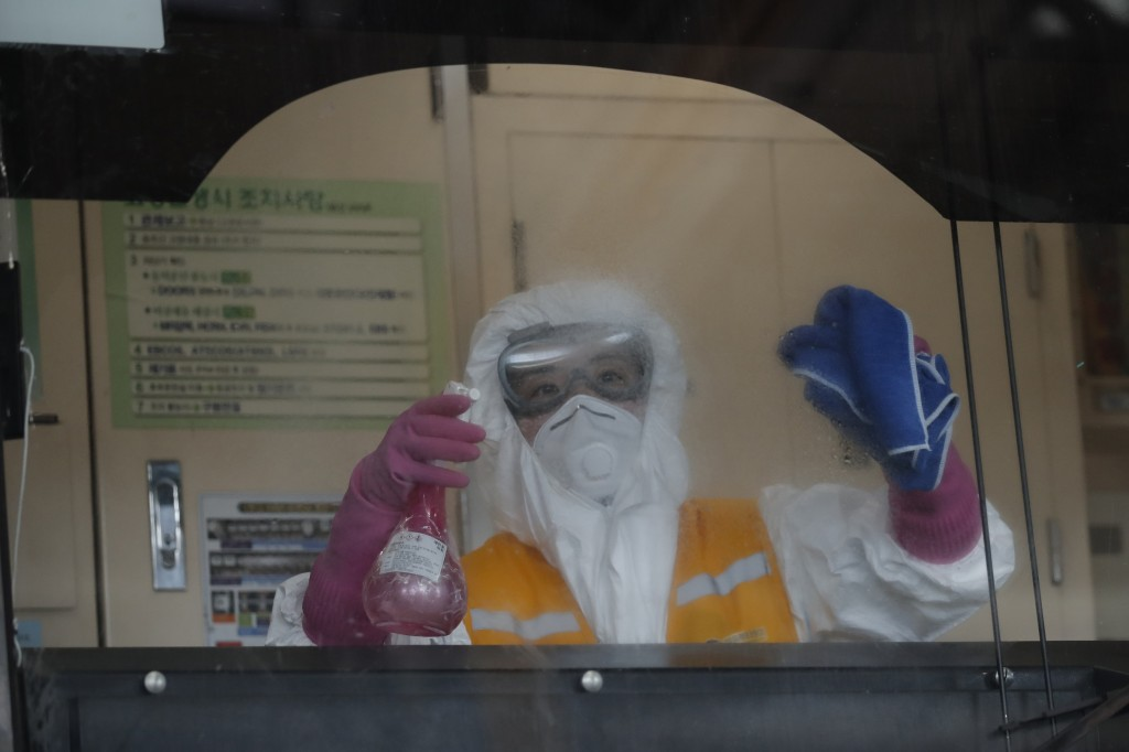 A worker wearing protective gears disinfects as a precaution against the new coronavirus at a subway car depot in Seoul, South Korea, Wednesday, March...