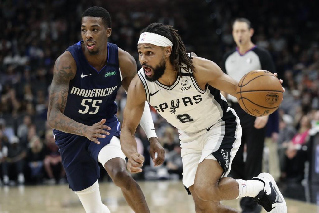 San Antonio Spurs guard Patty Mills (8) drives around Dallas Mavericks guard Delon Wright (55) during the second half of an NBA basketball game in San...