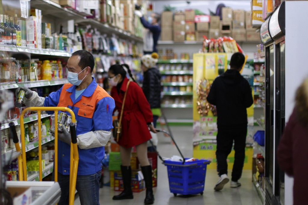 Staff and shoppers wear face masks inside a supermarket in Madrid, Spain, Wednesday, March 11, 2020. Spain's health minister on Monday announced a sha...