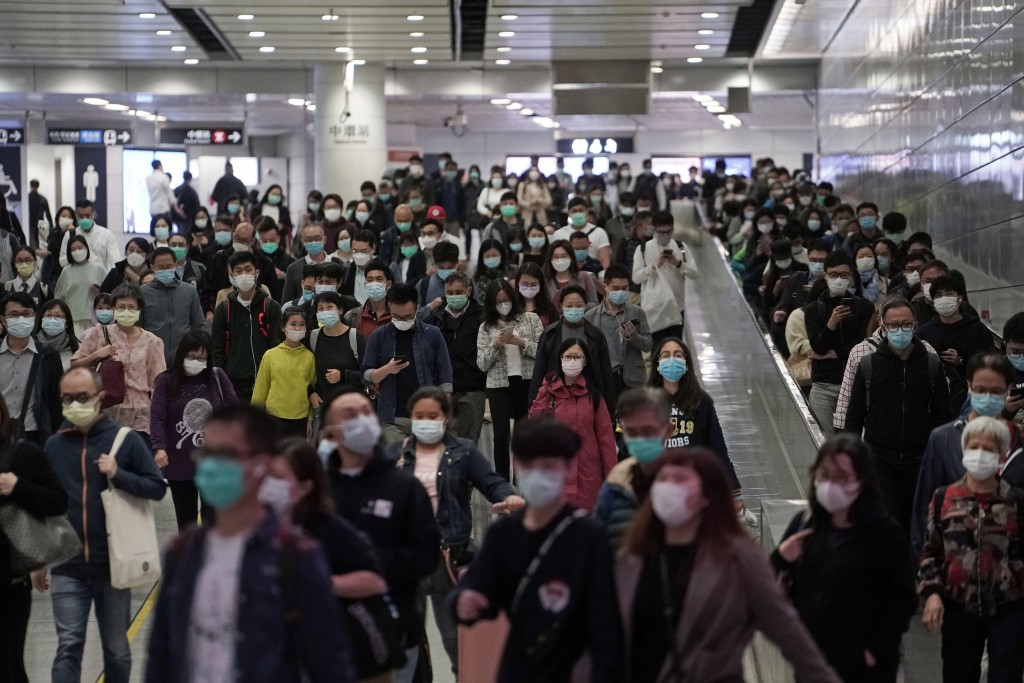 Commuters wear face masks as a precaution against the COVID-19 illness inside a subway station during rush hour in Hong Kong, Wednesday, March 11, 202...