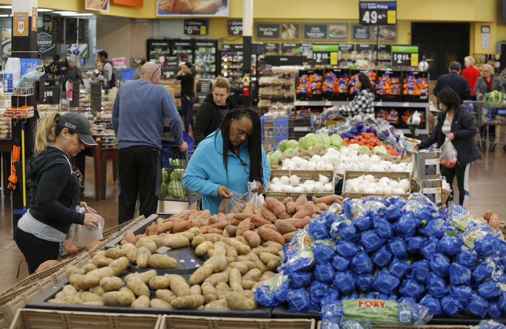 FILE - In this Nov. 27, 2019, file photo people shop for food the day before the Thanksgiving holiday at a Walmart Supercenter in Las Vegas.  U.S. con...
