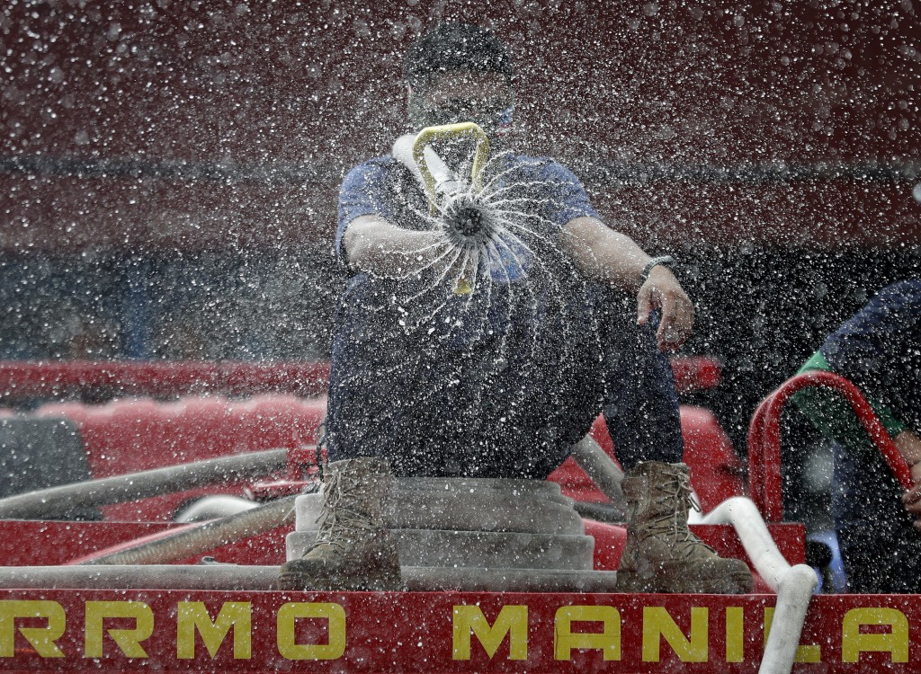 Firemen spray disinfectants outside a public market in Manila, Philippines on Wednesday, March 11, 2020. For most people, the new coronavirus causes o...